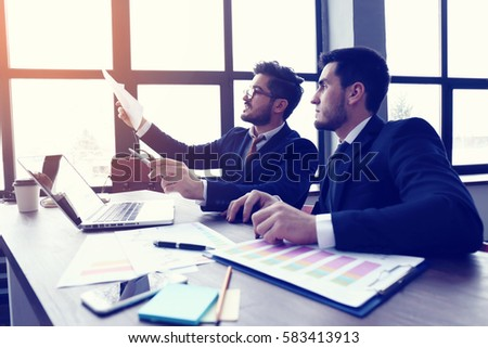 two young businessmen working on laptop at  modern office. Beard hipster businessmen. Film effect, lens flare  #583413913