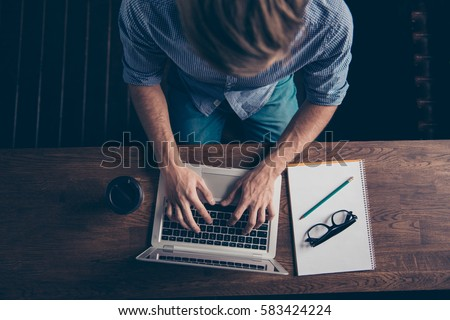 Top view of a youg guy searching for the information and drinking coffee
