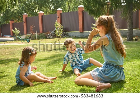 happy playful children outdoors in the summer on the grass in a backyard #583481683