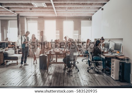 Office life. Group of young business people in smart casual wear working together in creative office #583520935