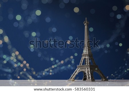 Souvenir Eiffel Tower on a dark blue background with colorful bokeh lights #583560331