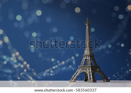 Souvenir Eiffel Tower on a blue background with colorful bokeh lights #583560337