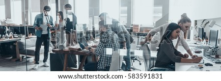 Office life. Group of young business people working and communicating together in creative office Royalty-Free Stock Photo #583591831