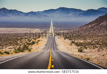Classic panorama view of an endless straight road running through the barren scenery of the American Southwest with extreme heat haze on a beautiful hot sunny day with blue sky in summer Royalty-Free Stock Photo #583717516