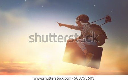 Dreams of travel! Child flying on a suitcase against the backdrop of sunset. Royalty-Free Stock Photo #583753603