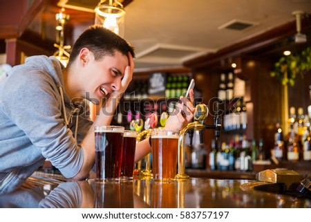 Young man having a stress. Drinking a beer and using phone #583757197