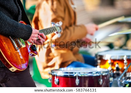 Festival music band. Hands playing on percussion instruments in city park . Drums with sticks closeup. Body part of male musicians. Sharpen is guitar and man hand. #583766131