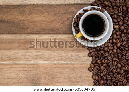 Cup of coffee with coffee beans on wooden background #583804906