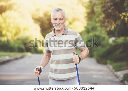 Joyful pleasant man using poles #583812544