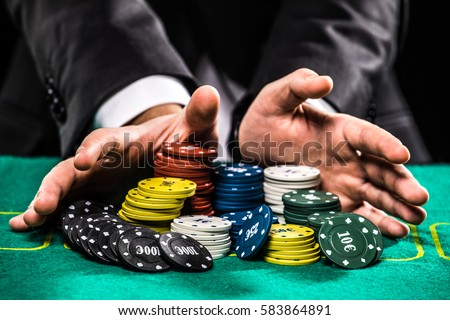 casino, gambling, poker, people and entertainment concept - close up of poker player with chips at green casino table Royalty-Free Stock Photo #583864891