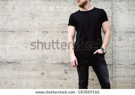 Young muscular bearded man wearing black tshirt and jeans posing in center of modern city. Empty concrete wall on the background. Hotizontal mockup #583869166