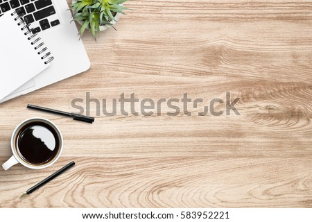 Wood office desk table with laptop, cup of coffee and supplies.   Royalty-Free Stock Photo #583952221