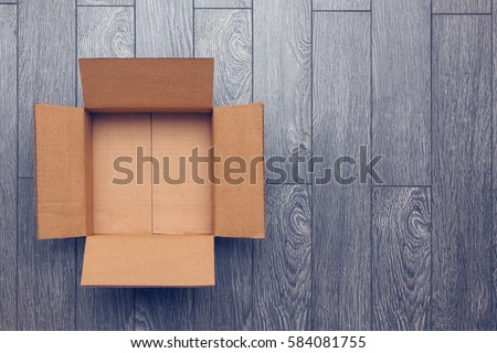 Flat lay of empty open cardboard box on wooden surface with empty space #584081755