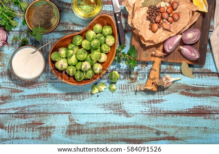 Brussels sprouts with ingredients for cooking tasty and healthy food on wooden table with border, top view. Healthy food #584091526