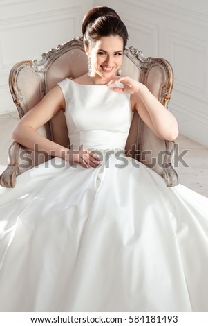 portrait of beautiful brunette bride with elegant hairstyle and makeup wearing long luxury wedding dress #584181493