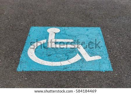 sign on the asphalt parking for disabled #584184469