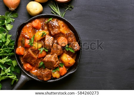 Beef stew with potatoes, carrots and herbs on black background with copy space, top view #584260273