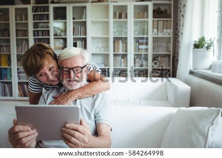 Senior couple using digital tablet in living room #584264998