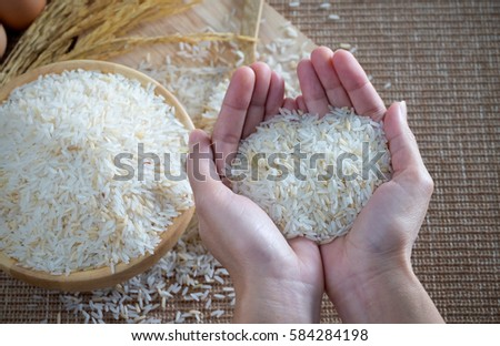 White rice on hand with sackcloth background. top view #584284198