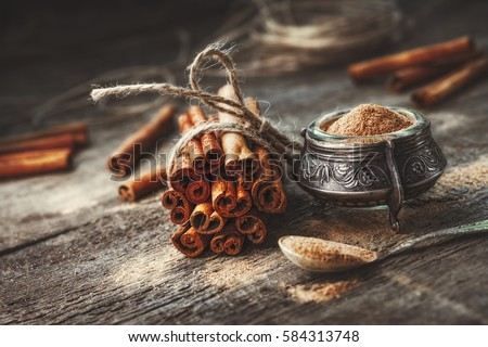 Ground cinnamon, cinnamon sticks, tied with jute rope on old wooden background in rustic style Royalty-Free Stock Photo #584313748