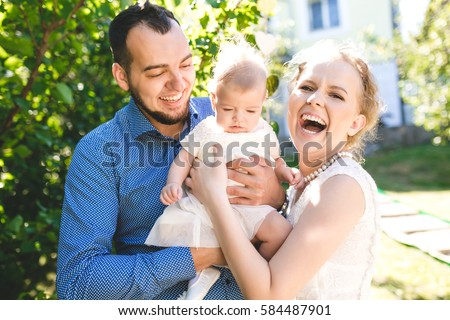 Happy joyful young family with child. Father, mother and little boy having fun outdoors in orchard garden, playing together in summer park. Mom, Dad, baby laughing and enjoying nature #584487901