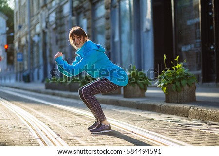 Young fitness woman in blue hoody doing squatting  exercise on the road of old city. Woman fitness sunrise workout outside wellness concept. #584494591