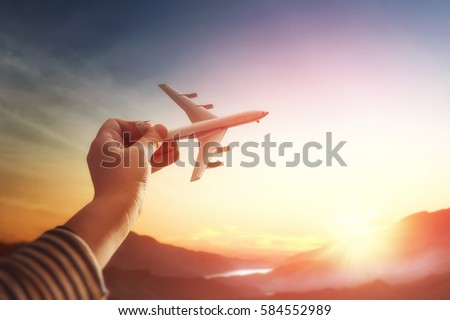 Child plays with a toy airplane in the sunset and dreams of journey. Hand with small plane close up. #584552989