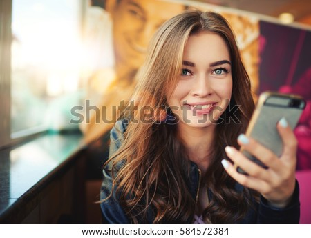 Smiling hipster girl is reading pleasant text message from her friend on mobile phone, while is sitting in cafe. Cheerful girl is watching funny video on cell telephone during free time in coffee shop #584572384