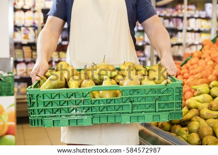 Salesman Carrying Pears In Crate At Grocery Store #584572987