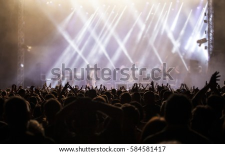 Photo of many people enjoying rock concert, crowd with raised up hands dancing in nightclub, audience applauding to musician band, night entertainment, music festival, happy youth, luxury party #584581417