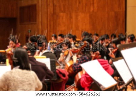 People playing music instruments inside a concert hall theme creative abstract blur background with bokeh effect #584626261