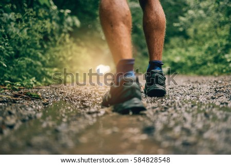 Muscular calves of fit male jogger training for cross country forest trail race in the rain on a nature trail. #584828548