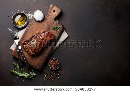 Grilled ribeye beef steak, herbs and spices. Top view with copy space for your text #584833297