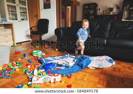 Adorable 1 year old baby boy with funny facial expression playing in a very messy living room Royalty-Free Stock Photo #584849578