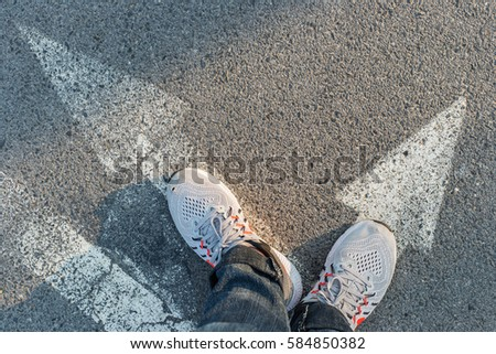 foot stand on asphalt pavement with white arrows pedestrian crossing road marking for background & texture #584850382