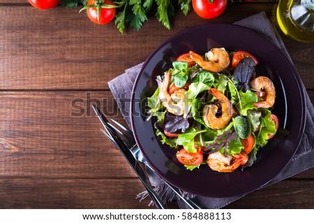 Fresh salad plate with shrimp, tomato and mixed greens (arugula, mesclun, mache) on wooden background top view. Healthy food. Clean eating. #584888113