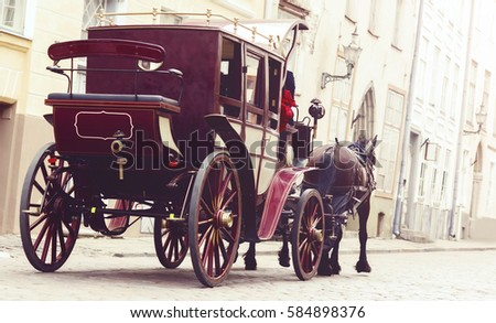 Horse and a beautiful old carriage in old town.  Royalty-Free Stock Photo #584898376
