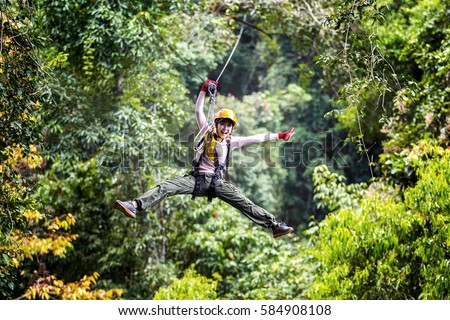 TOURIST adult wearing casual clothes Zip Line On Focus FOREST TRIP fun. #584908108
