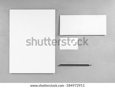 Blank stationery template for placing your design. Photo of blank stationery set. Blank letterhead, business cards, envelope and pencil. Mockup for branding identity. Top view. Grayscale image. Royalty-Free Stock Photo #584972911
