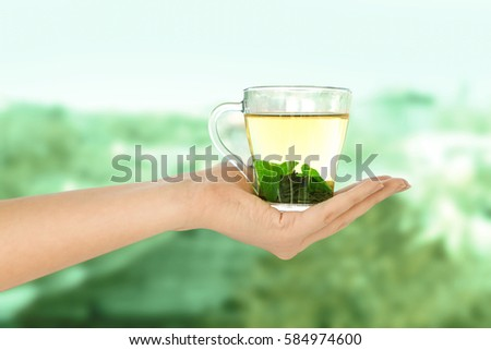 Woman holding cup of tea on blurred background #584974600