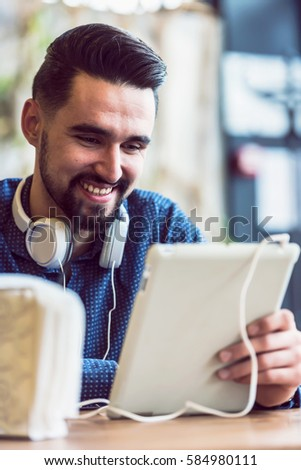 Handsome Modern Man using Tablet in Coffee Shop  #584980111
