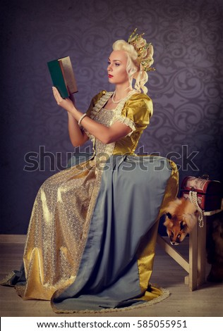 Picture of beautiful haughty queen in royal dress reading book