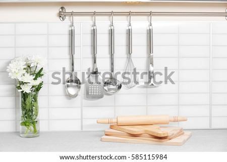 Set of metal kitchen utensils hanging on wall #585115984