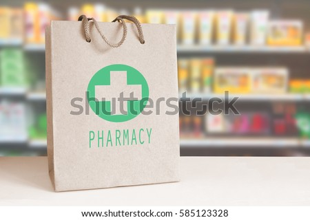 Recycled paper bag with a green Pharmacy logo in a drugstore. Empty copy space for Editor's content.. Royalty-Free Stock Photo #585123328