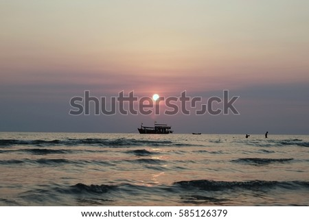 Fishing boats floating in the sea with the sun falling behind. #585126379
