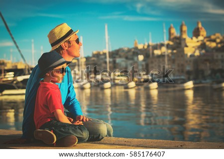 father and son looking at city of Valetta, Malta #585176407