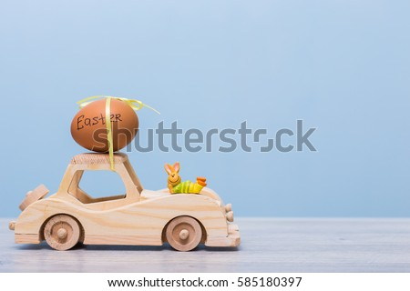 Easter eggs and bunny on wooden toy car. Abstract retro concept. delivering Easter eggs.
