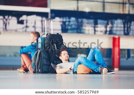 Two friends traveling together. Travelers waiting at the airport departure area for their delay flight. Royalty-Free Stock Photo #585257969