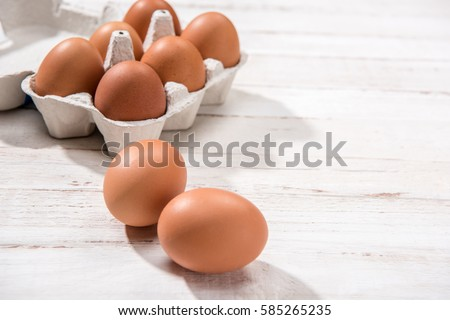 Close-up view of raw chicken eggs in egg box on white wooden background Royalty-Free Stock Photo #585265235