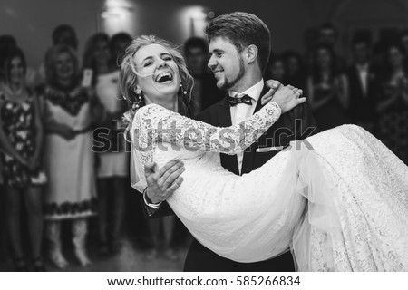Groom admires happy bride laughing in his arms #585266834